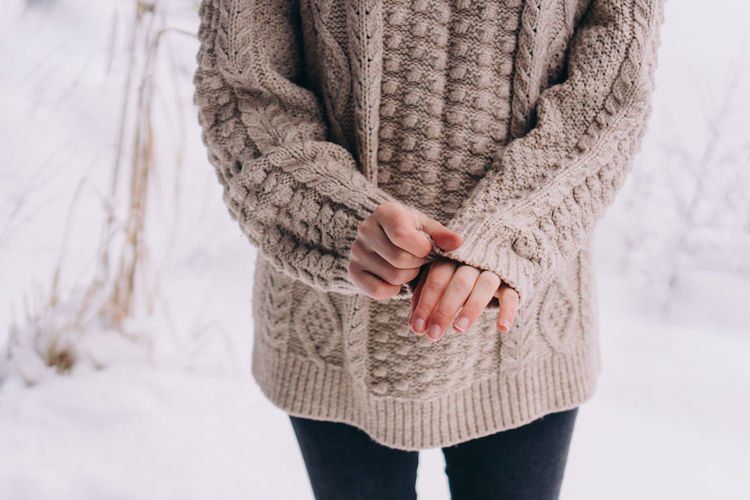 Midsection of woman standing in snow
