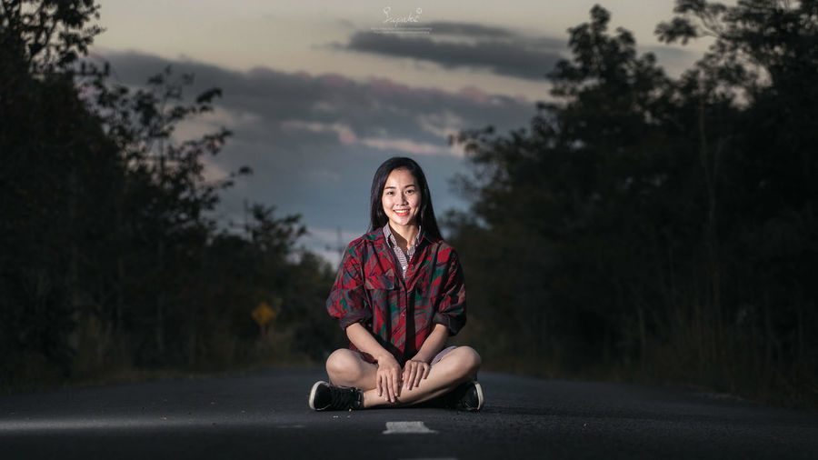 Portrait of woman sitting on road