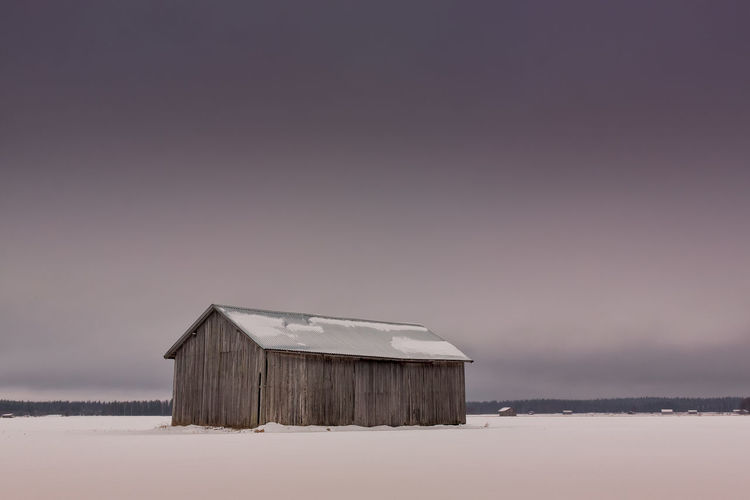 Barn on field against sky during winter