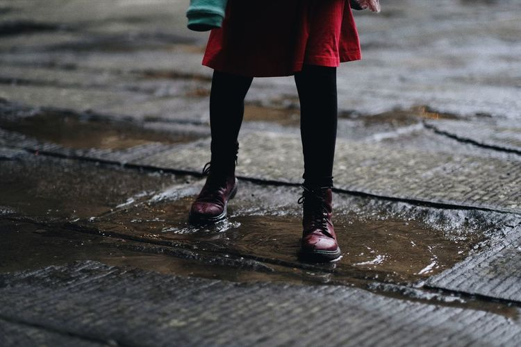 Low Section Of Woman Walking On Puddle During Rainy Season
