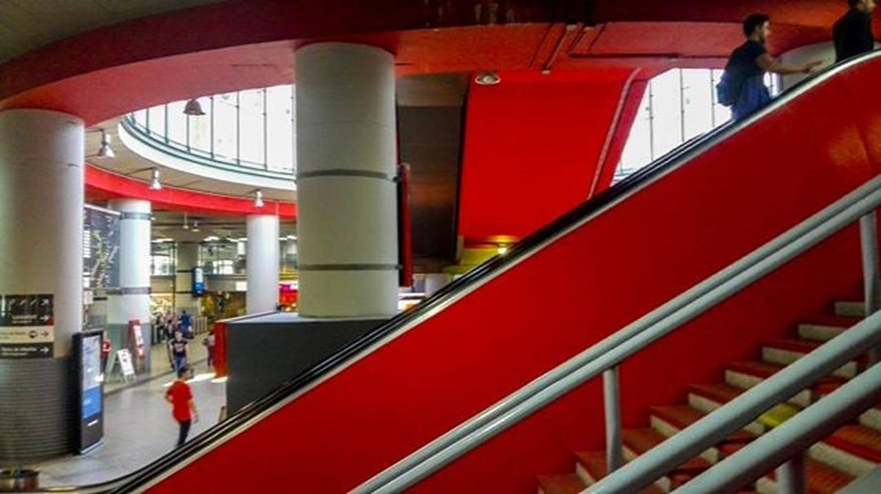 indoors, red, railing, steps, men, staircase, steps and staircases, person, built structure, architecture, lifestyles, incidental people, leisure activity, architectural column, escalator, metal, standing, day