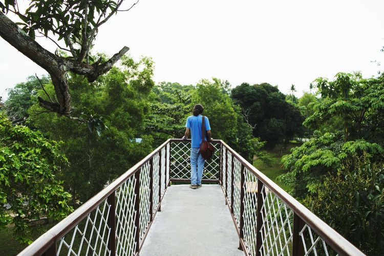 Rear View Of Man Standing On Footbridge Against Clear Sky