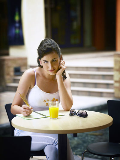 Portrait of young woman sitting at outdoor restaurant