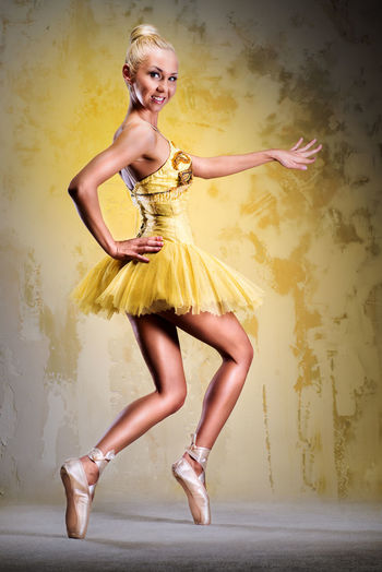 Portrait of beautiful ballerina dancing against yellow background