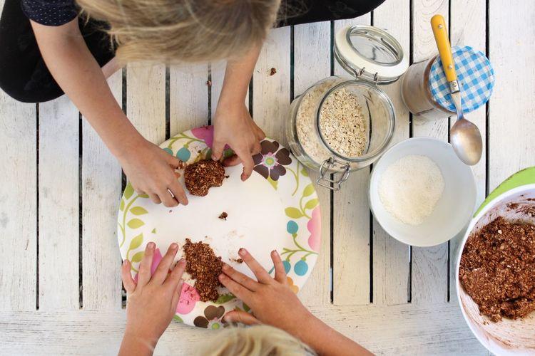 Children preparing food in plate on table