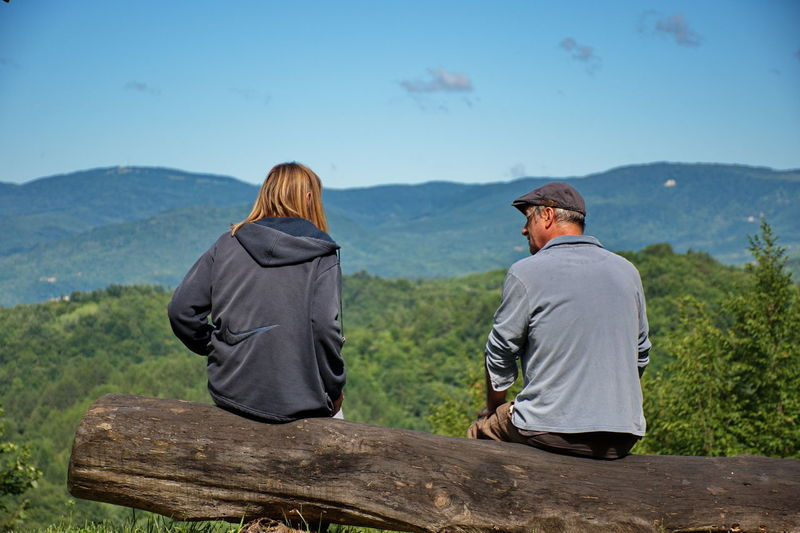 Senior couple sitting on tree trunk and looking over hills