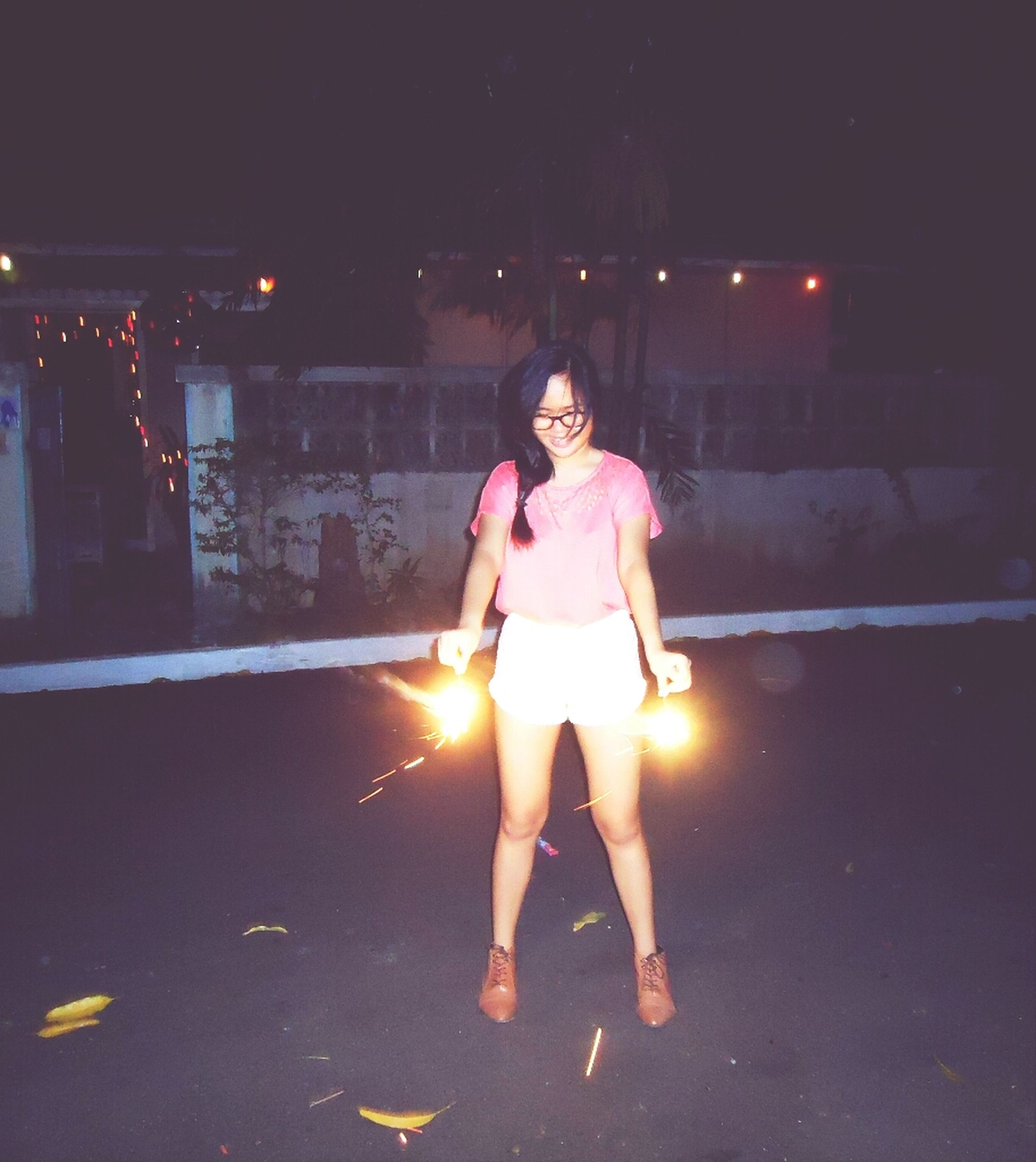 person, lifestyles, young adult, front view, young women, looking at camera, portrait, leisure activity, casual clothing, standing, happiness, smiling, illuminated, full length, night, three quarter length, holding