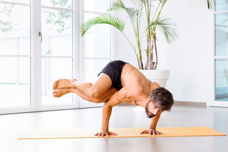 Full length of shirtless man exercising at home