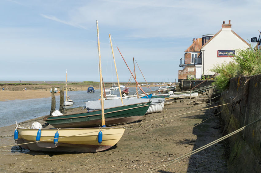 Fishing village in Norfolk, UK. In the summertime, with boats fishing nets. Also a beach next door to this beautiful place. Beach Blue Sky White Clouds Bushes With Fresh Green Leaves Coastline Grass Norfolk Uk Outdoor Photography Pebble Beach Sea Trees Water Waterfront