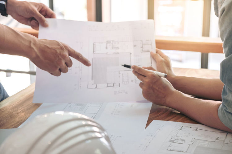 Industrial Industry Architecture Blueprint Close-up Design Designer  Diagram Draw Drawing Engineer Engineering Human Body Part Human Hand Indoors  Men Paper People Plan Planning Pointing Real People Structure Table Two People