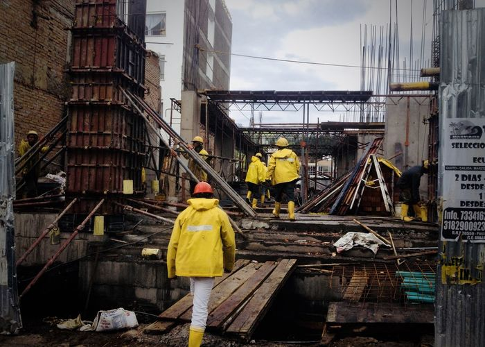Worker Working Adult Architecture Building Exterior Built Structure City Day Destruction Men One Person Outdoors People Real People Rear View Reflective Clothing Riot Sky Yellow