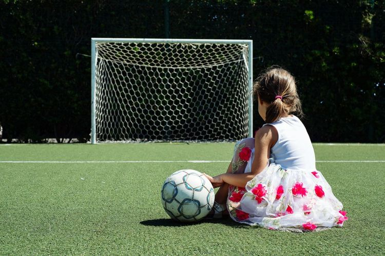 Low angle view of girl playing soccer on field