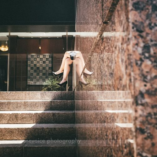 Side view of woman on staircase against wall