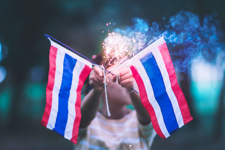 Girl holding sparkler with thai flags during celebration event