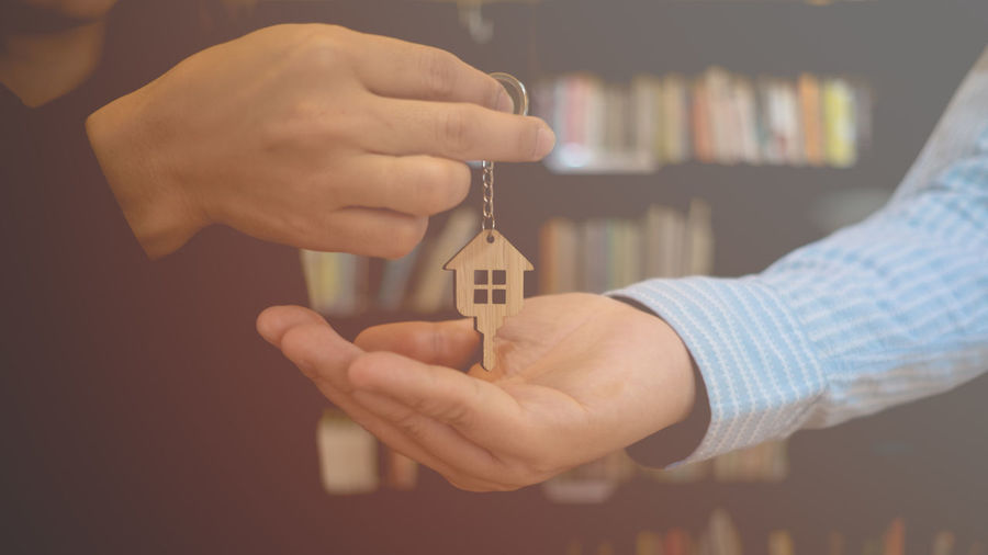 Midsection Of Real Estate Agent Giving Key To Man In Office