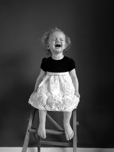 Cute Crying Girl Sitting On Stool At Home