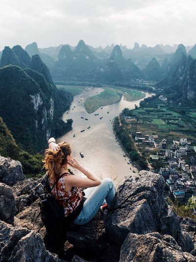 High Angle View Of Woman Sitting On Cliff Against Valley