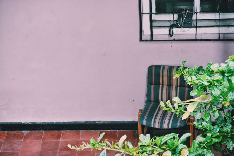 Chair at porch against pink wall