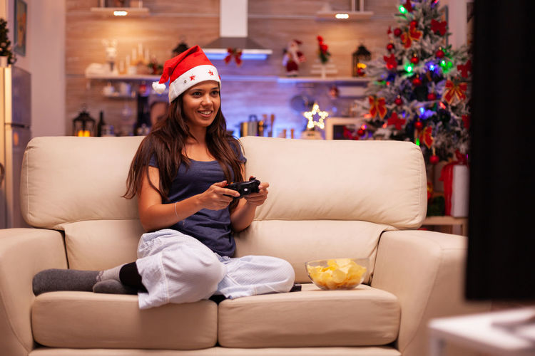 Young woman using phone while sitting on sofa at home