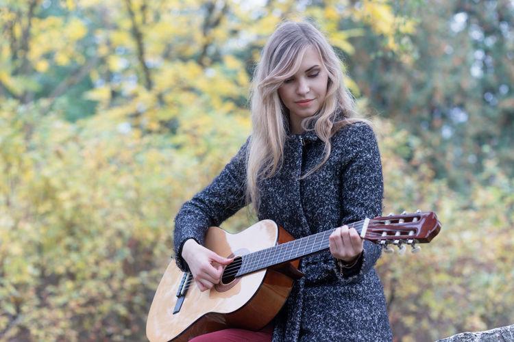 Beautiful young woman playing guitar outdoors