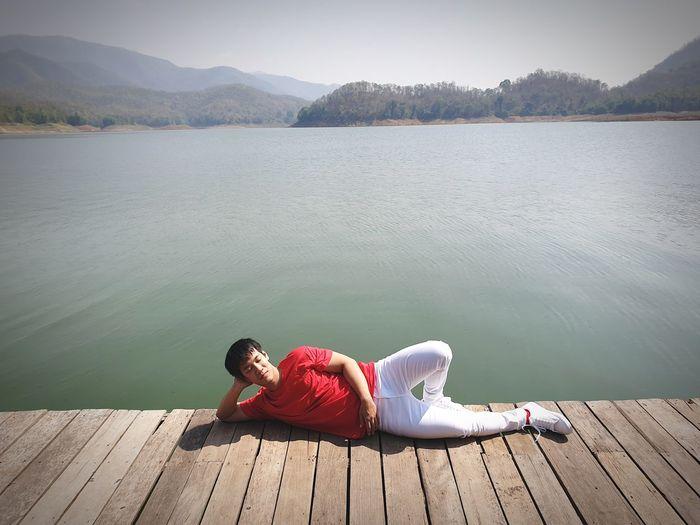 Man relaxing on pier at lake