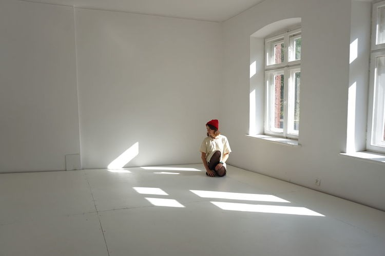 Full length of man woman looking away while sitting on floor at home