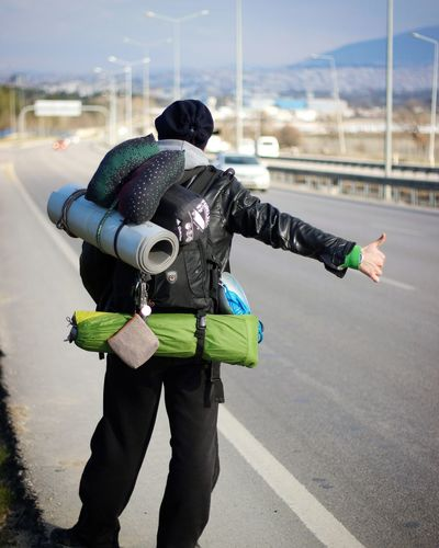 Rear view of backpacker hitchhiking while standing on street