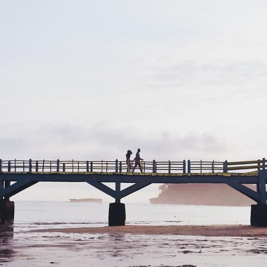 Couple walking on bridge over beach against sky