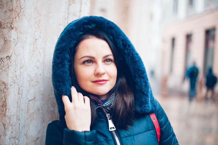 Beautiful woman in fur coat standing against wall