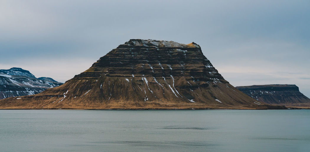 You know that famous cone shaped mountain in Iceland called Kirkjufell? This is how it looks from the side. Find more travel inspiration at http://www.instagram.com/simonmigaj Iceland Kirkjufell Travel Beauty In Nature Cold Temperature Environment Formation Idyllic Landscape Mountain Mountain Peak Mountain Range Nature No People Non-urban Scene Outdoors Scenics - Nature Sky Snow Snowcapped Mountain Tranquil Scene Tranquility Water Waterfront Winter