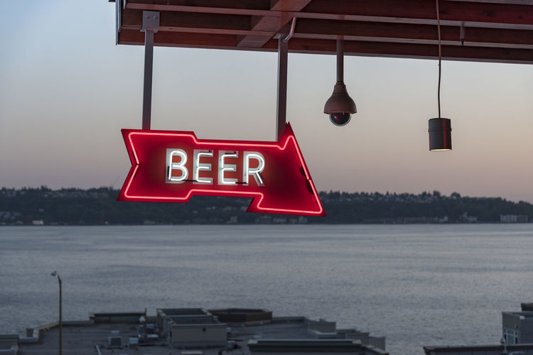 Illuminated signboard hanging against sea