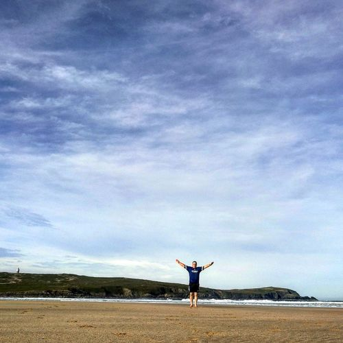Distant view of man with arms outstretched standing at beach against sky
