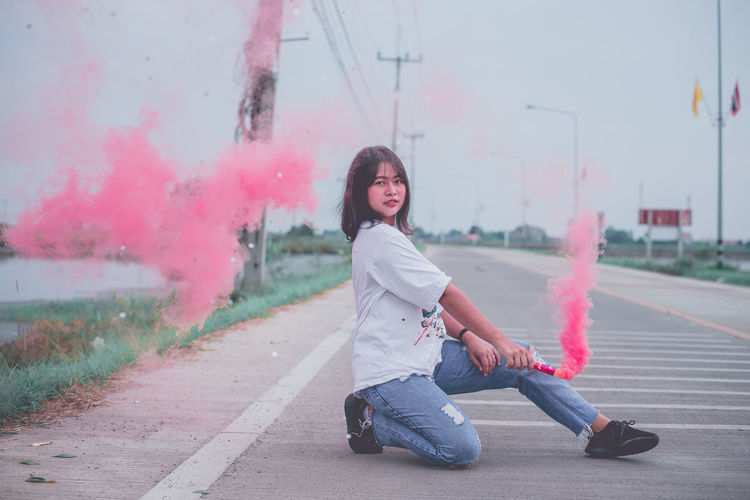 Portrait of young woman holding smoke bomb on road