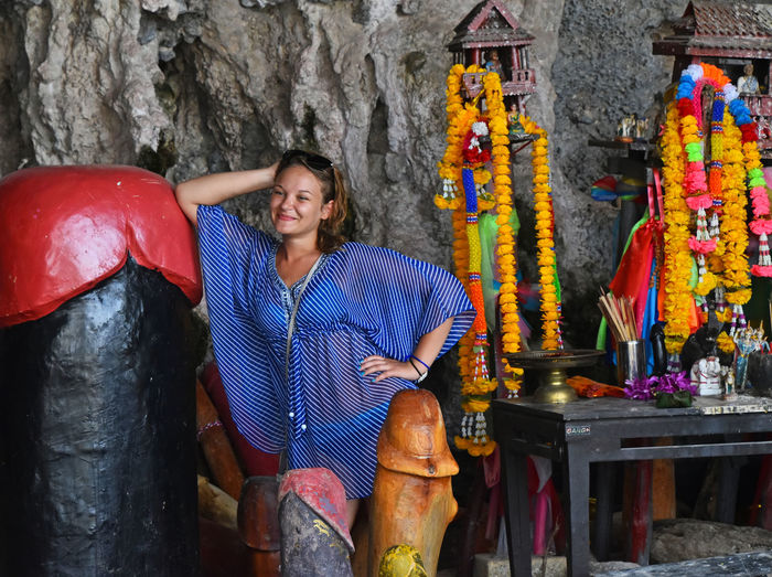 Irreverent tourists pose with wooden sacred religious attributes in front of cameras at Princess Cave shrine temple, Railay, Krabi, Thailnd, September 2015 Church Dishonor DISRESPECT Disrespectful  Irreverent Krabi Krabi Thailand Lack Of Culture Phranang Phranang Cave Pose Poser Posing Posing For The Camera Princess Cave Profanity Russian Srine Temple Thailand The Tourist Tourists Telling Stories Differently