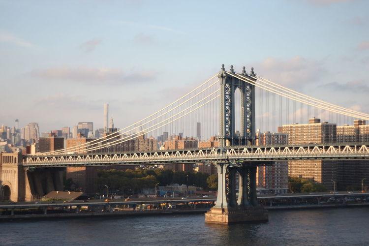 Manhattan bridge over east river in city against sky