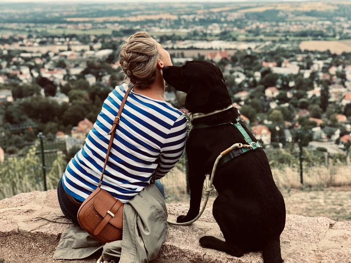 Rear view of woman with dog sitting on rock