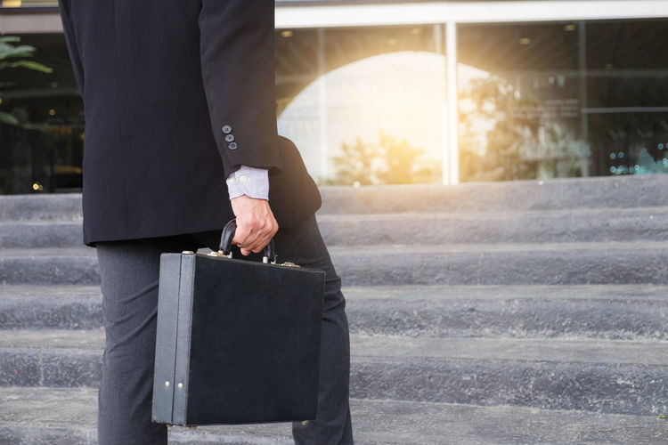 Midsection Of Businessman Standing With Briefcase Against Steps
