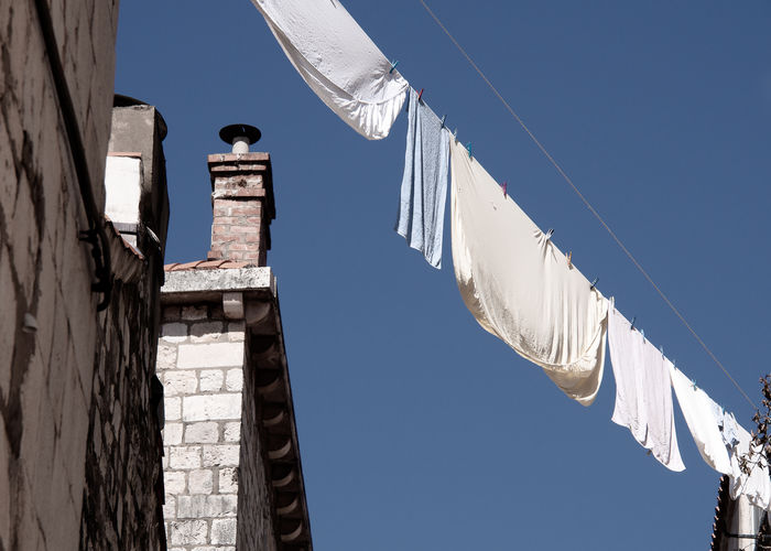 hanging clothes EyeEm Best Shots EyeEmNewHere Laundry Architecture Blue Blue Sky Building Exterior Built Structure Clear Sky Cloth Clothes Line Day Hanging Hanging Clothes Lighting Equipment Low Angle View No People Sunlight