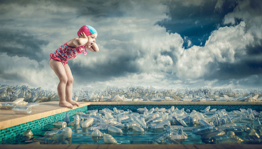 Side view of shocked girl looking at plastic bottles in swimming pool against cloudy sky