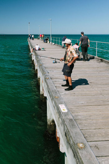 Escapism Getting Away From It All Horizon Over Water Incidental People Jetty Men Nautical Vessel Ocean Outdoors Pier Railing Recreational Pursuit Rippled Sea The Way Forward Vacations Walkway Water Weekend Activities Wood