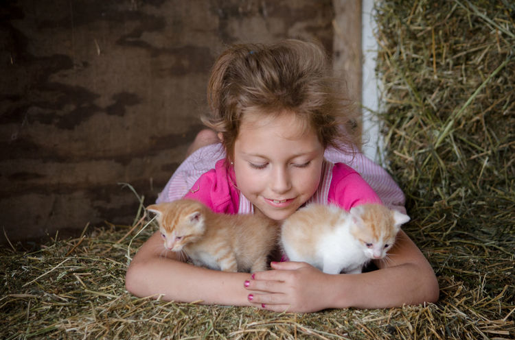 a cute little girl holds tiny kittens just discovered in the family barn Child Childhood Children Only Domestic Animals Family Farm Girls Little Mammal New Baby One Person Overalls People Pets Pink Color Streetphotography