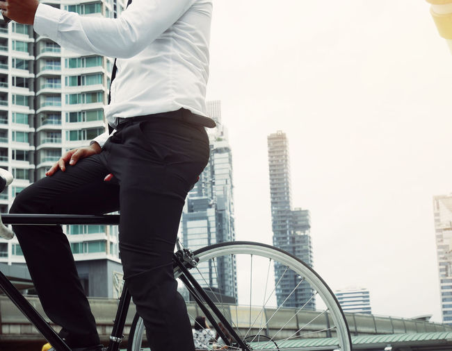 Business man riding bicycle go to worker. Architecture Building Building Exterior Built Structure Business City Day Lifestyles Men Modern Motion Nature Office Office Building Exterior One Person Outdoors Railing Real People Skyscraper Three Quarter Length