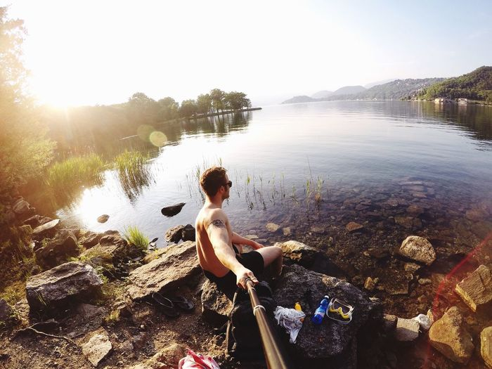 Shirtless Man Taking Selfie Using Monopod While Sitting On Rock By Lake