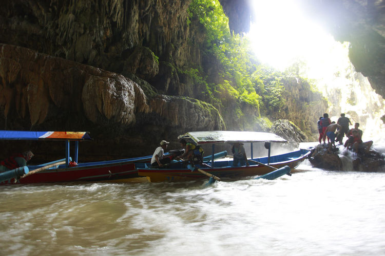 """Local tourists ride on boats Green Canyon at Cijulang Pangandaran, West Java, Indonesia, if in the summer the river is green. Green Canyon, popularized by the French in 1993, has a charm that is extraordinary. A combination of rivers, green valleys, forests, and various flora and fauna. The beauty wrapped in silence, like a hidden paradise. Its original name was """"Cukang Taneuh"""". Green Canyon has its own uniqueness. INDONESIA Taxi Boat West Java  Adventures In The City Boat Mode Of Transportation Nature Outdoors Rivers Transportation Water"""
