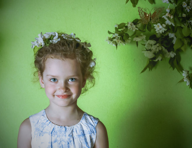 Portrait of girl wearing flowers while standing against wall