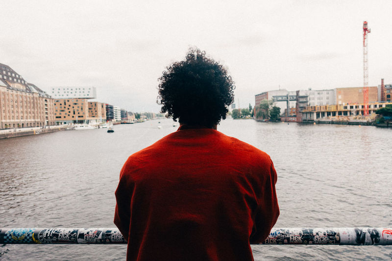 Rear view of man looking at city by river against sky
