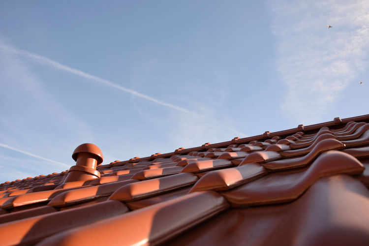 A roof against the sky Sky Roof Cloud - Sky No People Day Roof Tile Ceramic Tiles Nature Low Angle View Built Structure Selective Focus In A Row Architecture Outdoors Building Exterior Brown Pattern Building Sunlight Blue Close-up Vapor Trail
