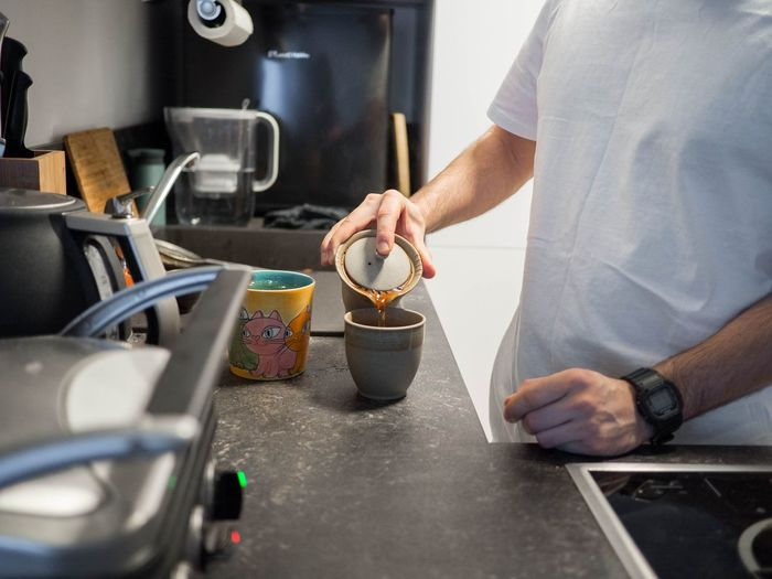 Midsection of man working with coffee at home