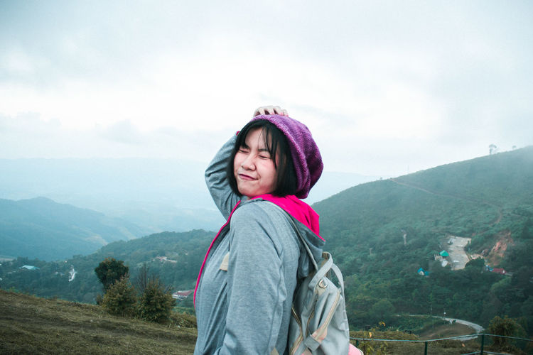 Backpacker making face while standing against mountain range against sky
