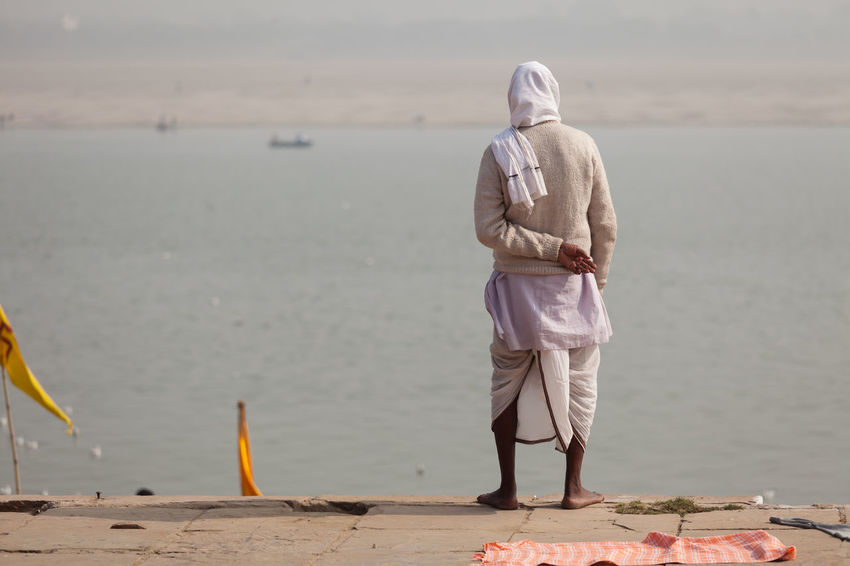 Man watching the Ganges river in Varanasi, India. ASIA Belief Ganga Hinduism Holi India People Religion River Sadhu Spirituality
